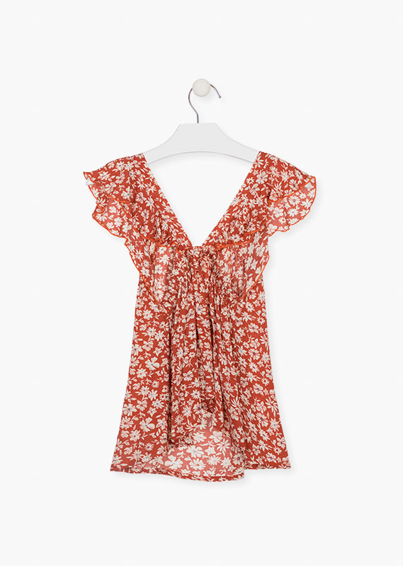 Sleeveless floral motif blouse.